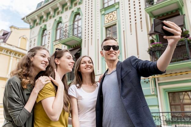 セルフィーを取る友人の低角度のグループ 無料写真