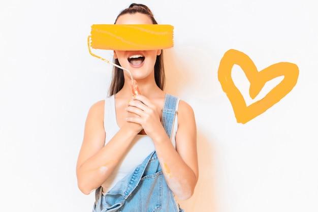 Счастливая женщина прячет лицо малярным валиком. оранжевое сердце на стене. концепция ремонта Premium Фотографии