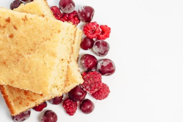 Торт манной крупы с малиной и вишней, изолированные на белой поверхности Premium Фотографии