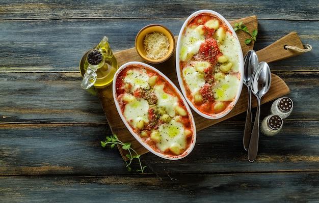 イタリアのジャガイモ団子のニョッキアッラソレンティーナとモッツァレラチーズをオーブンでトマトソースとハーブで焼きました。 Premium写真