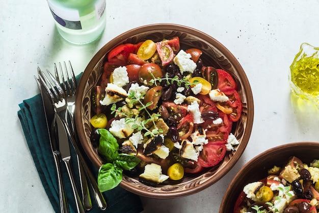 イタリアの伝統的なトスカーナのパンツァネラサラダ。フレッシュトマトとチーズとクレープレート、白ワインとボトルとグラス。 Premium写真