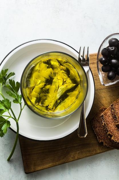 Сардины, маринованные в оливковом масле с ржаным хлебом, солью и перцем на столе Premium Фотографии