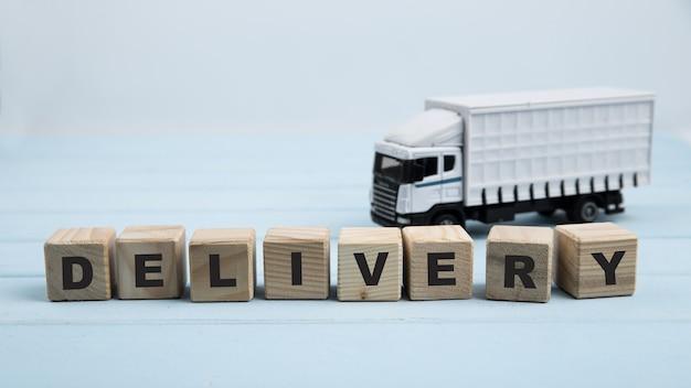 青色の背景に配送トラックグッズとスクエアキューブ Premium写真