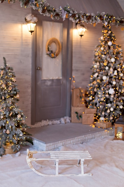 Дом в новогоднем стиле с елкой и гирляндами. снежная рождественская улица. Premium Фотографии