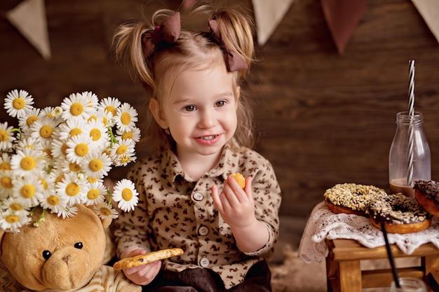 女の子はクッキーを食べ、テディベアを食べさせます。 Premium写真