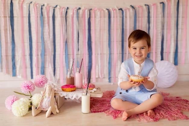 男の子はドーナツを食べ、ストローから牛乳を飲みます。子供のための素晴らしい食べ物。 Premium写真