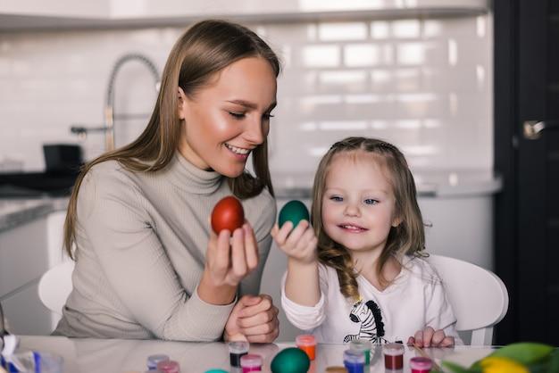 Мать и маленькая дочь с пасхальными яйцами и пасхальная корзинка на кухне готовы к пасхе Бесплатные Фотографии