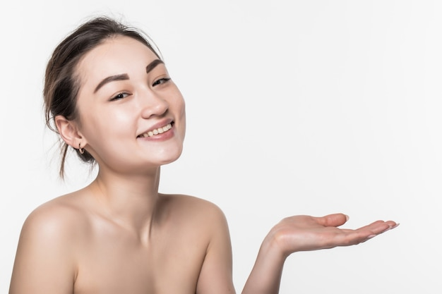 ボディスキンケアケア美容アジアの女性が開いた手の側に製品を表示して提示し、分離した白い壁を表示します。 無料写真