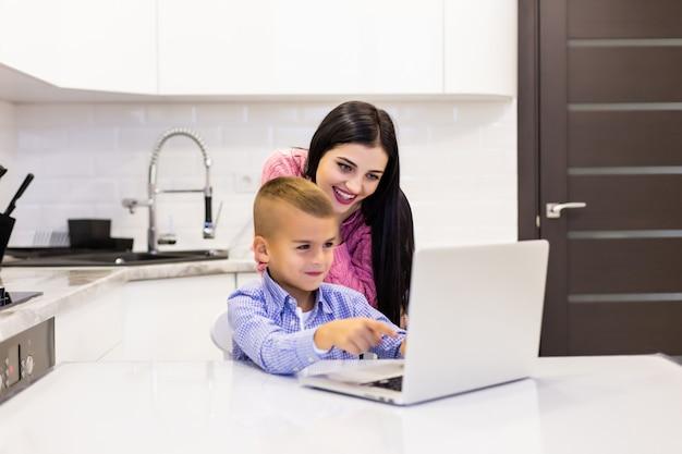 母親が息子が自分のラップトップを使って台所で勉強しているのを見落としている 無料写真