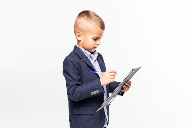 スーツの学校の少年は、白い壁に分離された空白のシートクリップボードを表示します。 無料写真