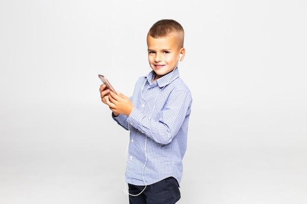 Маленький мальчик в наушниках слушает музыку изолирован на белой стене Бесплатные Фотографии