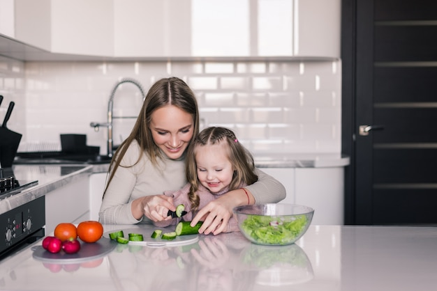母と子の娘が野菜サラダを準備しています 無料写真