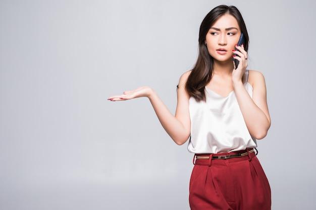 白い壁に分離された電話で若いアジアの女の子 無料写真
