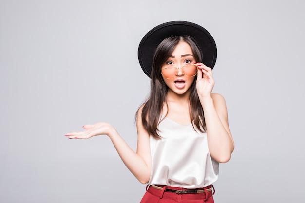 Молодая азиатская женщина с жестом солнечных очков при руки изолированные на белой стене Бесплатные Фотографии