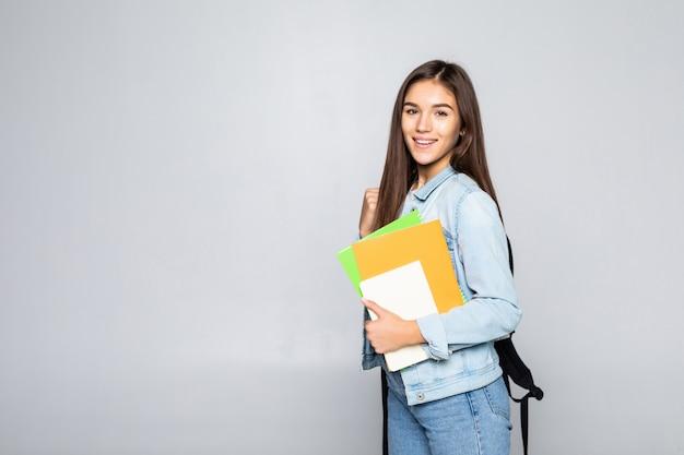 Портрет привлекательной милой молодой девушки студента, изолированных на белой стене Бесплатные Фотографии