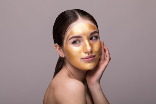 柔らかい肌にゴールドの化粧フェイスマスクを持つ健康な若い女性のクローズアップ。 無料写真