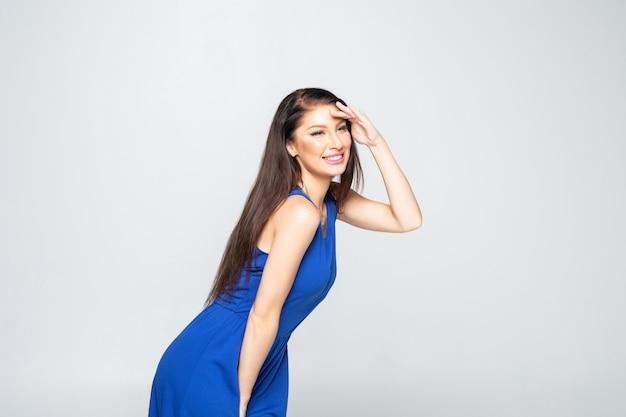 Счастливая игривая молодая женщина в платье стоит и смотрит далеко Бесплатные Фотографии