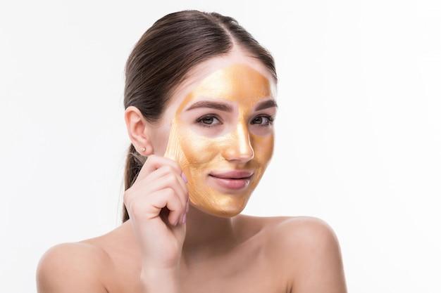 白い壁に分離された黄金の肌化粧品タッチの顔を持つ美しい女性。美容スキンケアと治療 無料写真