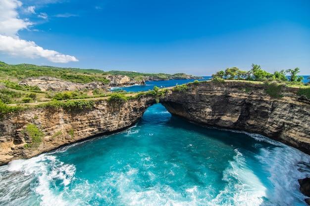 ヌサペニダ、バリ、インドネシアの壊れたビーチのパノラマビュー。青い空、青緑色の水。 無料写真