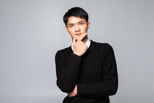 あごに孤立した白い壁の上に立って手を持つ若いアジア中国人男性 無料写真