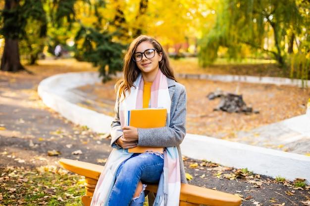 公園のベンチに座って、本を読んで若いきれいな女性。秋の時間。 無料写真
