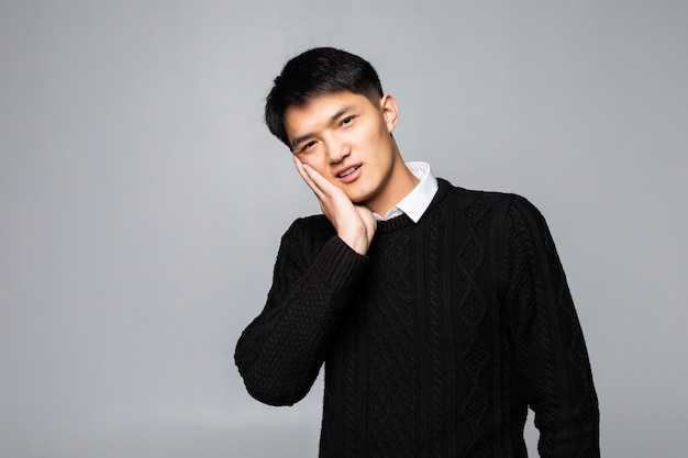 アジアの太った男性の肖像画は、歯痛で痛みを感じて、手を頬に当てます。口腔保健のコンセプトです。 無料写真