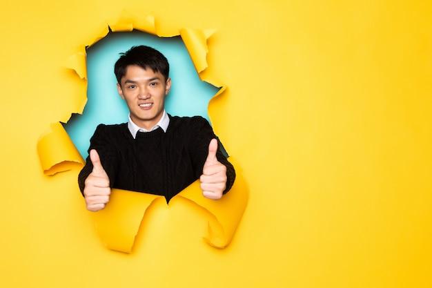 親指を持つ若い中国人男性は引き裂かれた黄色の壁の穴に頭を保ちます。破れた紙の男性の頭。 無料写真