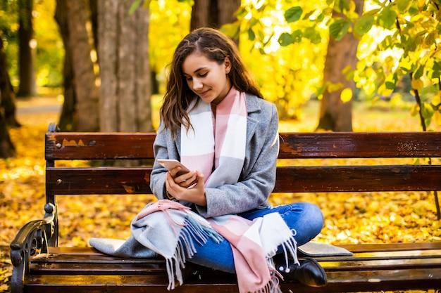 スマートフォンと都市の秋の公園のベンチに座っているテキストメッセージを使用して十代の少女 無料写真
