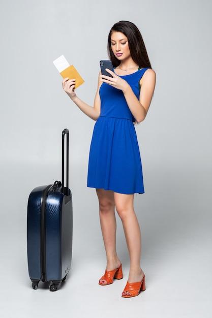 分離されたトラベルバッグとカジュアルなウォーキングで若い女性の完全な長さ 無料写真