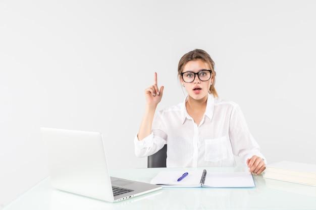 Молодая взволнованная женщина в пастельных одеждах, держащих указательный палец с большой новой идеей, сидит, работает за столом с ноутбуком, изолированным на сером фоне. достижение бизнес карьеры концепции. Бесплатные Фотографии