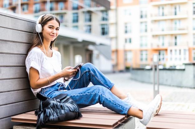 Молодая женщина с помощью мобильного телефона слушать музыку, сидя на скамейке в парке Бесплатные Фотографии