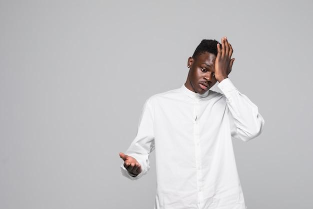 Футболка молодого афро-американского человека нося белая удивленная с рукой на голове для ошибки, вспоминает ошибку. забыл, плохая концепция памяти. Бесплатные Фотографии
