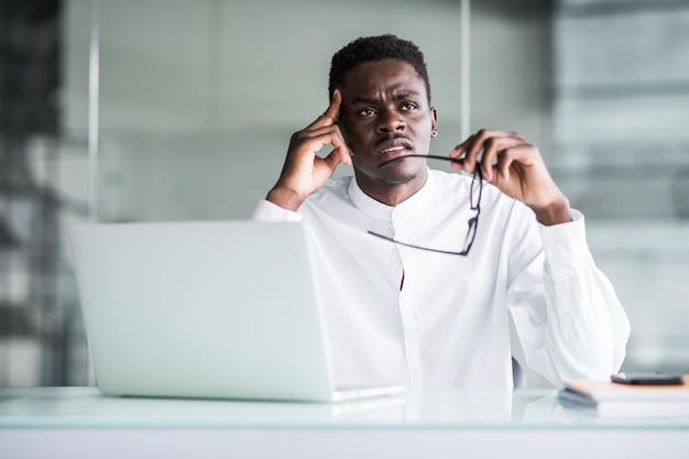 彼の職場で若いビジネスマンは、手で頭の痛みに触れる頭を感じます。ストレスワーク 無料写真