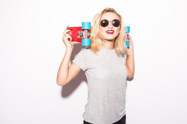 若い女性は彼女の頭の後ろに赤いスケートボードを保持します 無料写真