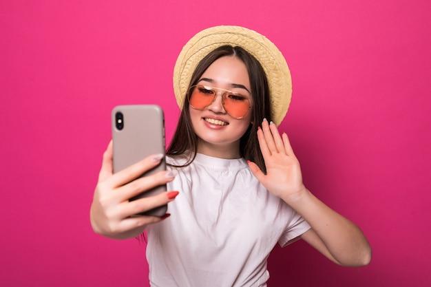 ピンクの壁のスマートフォンで挨拶するアジアの女性 無料写真