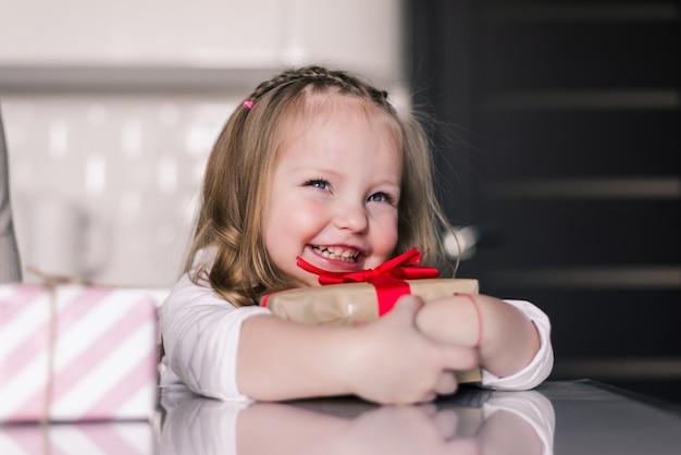 彼女の膝の上にプレゼントを押しながらキッチンに座って美しい小さな女の子 無料写真