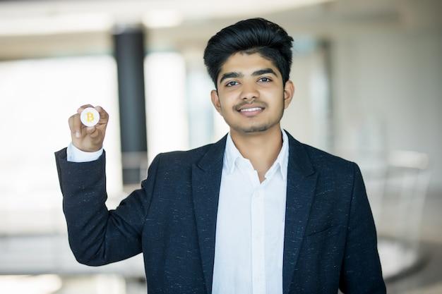 Индийский деловой человек в костюме с золотой биткойн в современном офисе Бесплатные Фотографии