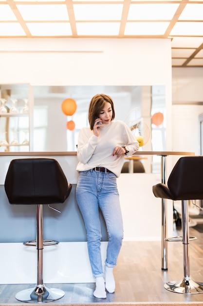 Красивая женщина разговаривает по телефону, стоя в панорамной кухне с яркими стенами, высоким столом и барными стульями Бесплатные Фотографии
