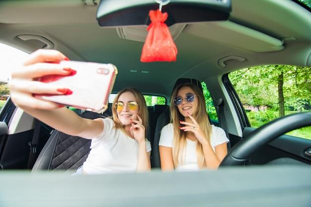 Пристанище двух молодых женщин в автомобильной поездке за рулем автомобиля и принимая селфи Бесплатные Фотографии