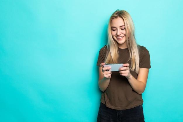 水色の壁に分離されたゲームデバイスガジェットを楽しんでいる肖像画の女性 無料写真