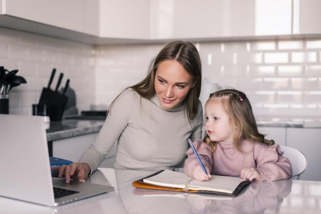 ダイニングルームのテーブルで宿題を娘を助ける若い母親 無料写真