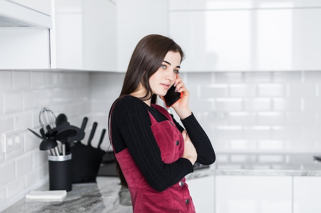 台所で調理する前に携帯電話で話している幸せな興奮した女性 無料写真