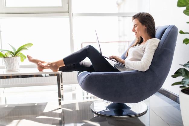 Молодая улыбающаяся брюнетка девушка сидит на современном стуле у окна в светлой уютной комнате дома работает на ноутбуке в расслабляющей атмосфере Бесплатные Фотографии