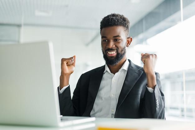 Счастливый афро-американский бизнесмен в костюме, глядя на ноутбук взволнован хорошие новости онлайн. чернокожий мужчина, сидящий за офисным столом, достиг цели, поднимая руки, празднуя успех бизнеса Бесплатные Фотографии
