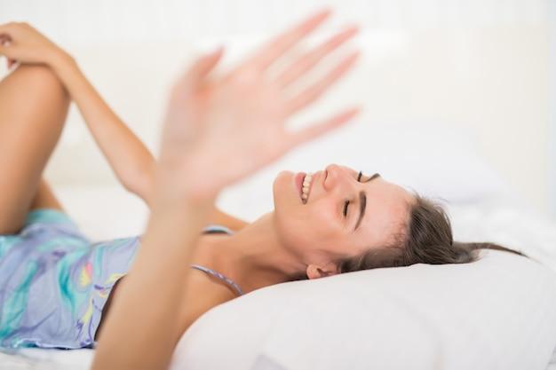 手で白いベッドとカバーカメラの下着姿で横になっている若いきれいな女性 無料写真