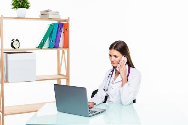 電話で誰かに電話して彼女のラップトップを使用しながら彼女の机に座っている深刻な女性医師 無料写真