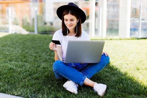 公園の緑の芝生に座っている間クレジットカードを保持していると購入のためのラップトップを使用して若いきれいな女性の摩耗 無料写真