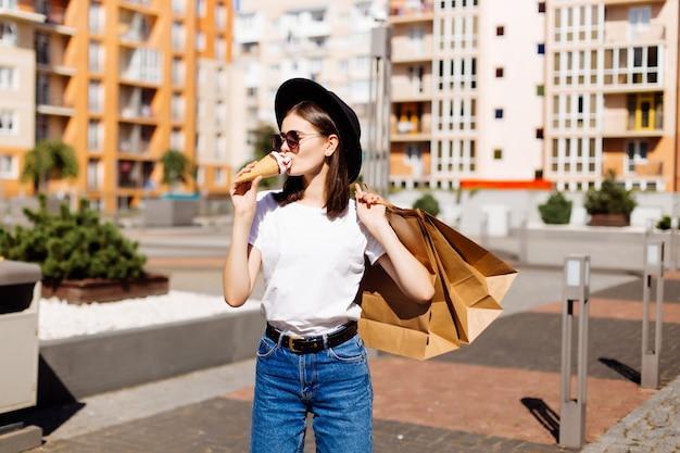販売、消費、夏、人々の概念。ショッピングバッグと街のアイスクリームと幸せな若い女 無料写真