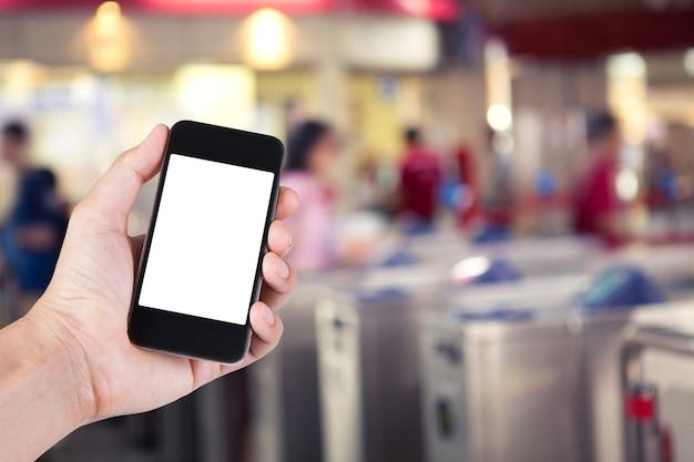 Человек, используя смартфон белый держатель экрана под рукой с размытым фоном людей, идущих мимо билетных автоматов в электропоезда. Premium Фотографии