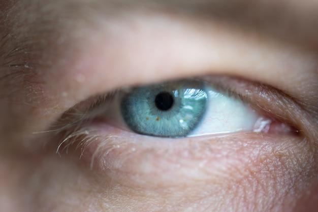 Голубые глаза мужчины крупным планом макро фон Premium Фотографии